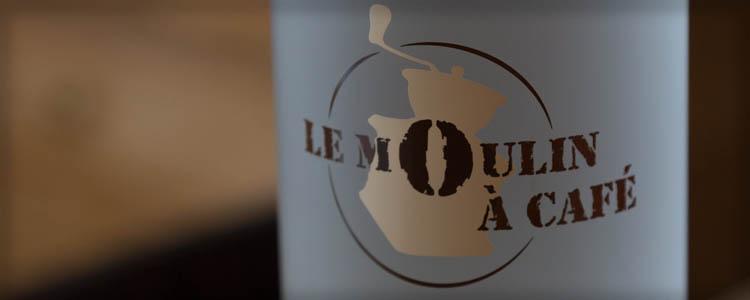 Gros plan d'une bouteille du restaurant avec le logo du moulin a café